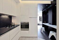 Breakfast bar and stools against dark wall in doorway leading from white minimalist designer kitchen