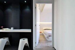 Custom white counter and black stools in black niche next to open bedroom door