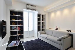 Pale couch, black rug and balcony door between white fitted shelves in modern living room