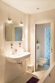 White mosaic tiles and sliding toilet door in bathroom