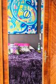Bed with purple fur blanket and colourful artwork reflected in mirror on wardrobe door