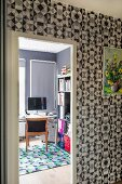 Wallpaper with graphic pattern in hallway and view into study through open door