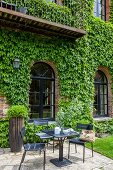 Seating area outside brick building with Virginia creeper on wall
