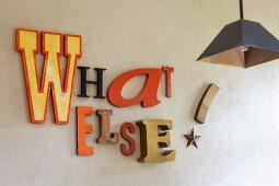 Verschiedene Reklamebuchstaben an der Wand als Spruch und Deko