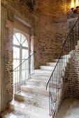 Geschwungene Steintreppe an einer rustikalen Backsteinwand