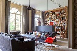 Wohnzimmer mit Raumteilerwand und deckenhohem Bücherregal