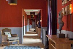 Langer Flur mit zweifarbig gestrichener Wand und Barocksessel