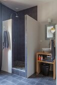 Dusche mit gemauerter Wand und dunklen Fliesen, Nische mit Waschbecken