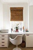 Weißer Schreibtisch mit Tulip Chair vor Fenster mit Bambusrollo und Retro-Flair