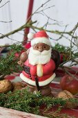 Chocolate Father Christmas amongst juniper branches and nuts