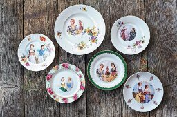 Printed round pictures of women wearing traditional costumes on various floral plates and