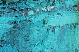 Abblätternde blaue Farbe an einer Wand