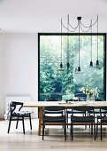 Essplatz mit schwarzen Stühlen um Edelholztisch unter Designer-Pendelleuchten vor raumhohem Fenster
