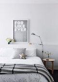 Doppelbett mit Tagesdecke und Kissen vor Betthaupt mit Ablagefläche