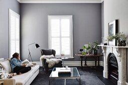 Elegantes, graues Wohnzimmer mit Frau auf Sofa vor modernem Glascouchtisch und Kamin
