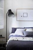 Bedroom with black floor lamp next to bed, framed picture with geometric shapes