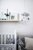 Children's room with white crib and gray armchair, storage and mobile with cloud motif above