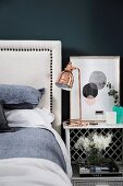 White bed with headboard next to bedside table with copper-colored table lamp against black wall