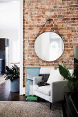 Round wall mirror on brick wall, including a white armchair in a renovated old building