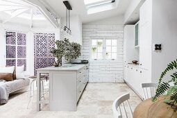 Open kitchen with light gray, freestanding counter in country house style in a restored old building