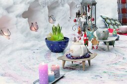 Teapots on decorated table in front of candle lanterns in niches sculpture from snow