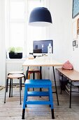 Dining and working area below window in period apartment; blue step-stool and table below black pendant lamp