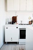 White kitchen area with wall cabinet and stylised face painted on base unit
