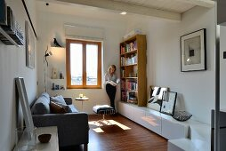 Woman reading between bookcase and windor in renovated living room