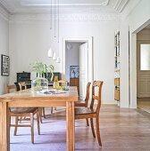 Holztisch und Stühle unter weissen Pendelleuchten im Esszimmer mit Stuckdecke und Klavier