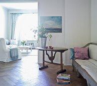 Wohnzimmer mit antikem Sofa und rustikalem Tisch, im Hintergrund weisser Polstersessel und Couchtisch vor Fenster