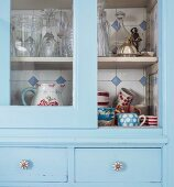 Pale blue, vintage kitchen dresser with open sliding glass door