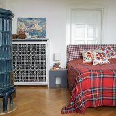 Wilhelmine-era tiled stove, bed with red tartan blanket and white panelled door in bedroom of period apartment