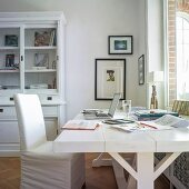White desk and loose-covered chair below window in rustic study