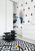 Child climbing wall bars in monochrome child's bedroom
