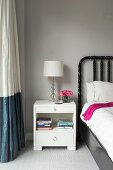 White bedside cabinet next to two-tone curtain