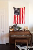 Piano and piano bench below flag of the United States on wall