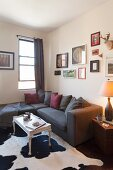Dark grey couch and coffee table on black and white cowhide rug in corner of living room