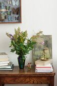 Vase of wildflowers and oak leaves next to stack of books