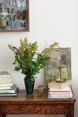 Strauß aus Wiesenblumen und Eichenblättern neben Bücherstapeln