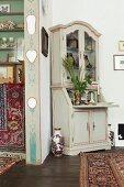 Antique corner cabinet next to painted doorway