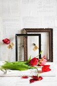 Red tulips in front of old picture frames against wall papered with book pages