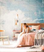 Junge Frau auf Doppelbett vor Studiowand mit Himmelmotiv