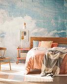 Doppelbett und Servierwagen als Nachttisch vor Studiowand mit Himmelmotiv
