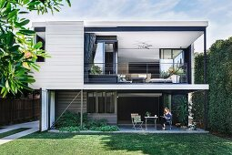 View from the garden of an elegant, cubic architect's house with terrace and spacious loggia