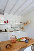 Walnuts and fresh fruit on wooden table in front of white kitchen counter below white wood-beamed ceiling