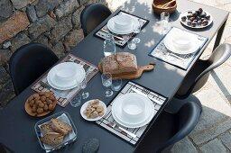 Blick auf gedeckten schwarzen Tisch mit weissem Geschirr auf Terrasse