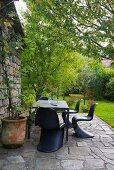 Outdoor Essplatz mit schwarzen Klassiker-Schalenstühlen auf Natursteinboden vor Rustiko