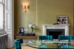 Glass table and green-painted wall in grand interior with fireplace