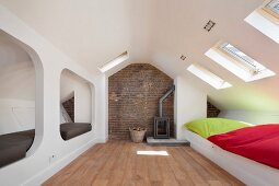 Modern alcoves and colourful cushions on integrated white benches below skylights in converted attic