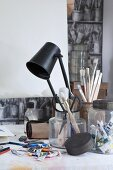 Artist's utensils in various storage jars, tubes of paint and black table lamp on desk